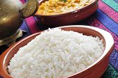 closeup of an earthenware bowl basmati rice and a bowl with korma curry in the background on a set t