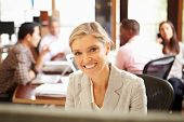 Businesswoman Working At Desk With Meeting In Background