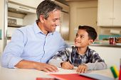 Hispanic Father Helping Son With Homework At Table