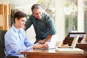 image of 16 year old  - Father And Teenage Son Looking At Laptop Together - JPG