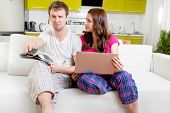 Young Married Couple In Pajamas Sitting In The Sofa With Newspaper And Laptop And Watching Tv At Hom