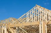stock photo of hurricane clips  - Frame construction of a truss roof with hurricane tie down clips for a house - JPG