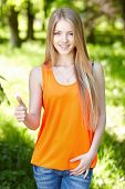 Smiling female outdoors gesturing thumb up