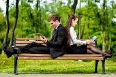 foto of work bench  - Young Business couple sitting on the bench and reading or working with tablets outdoors - JPG