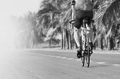 Young Man Riding Road Biking Bycycle On Asphalt Track In Black And White Motion Usse For Sport Activ