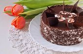 Chocolate Cake With Tilips On The Lace Napkin