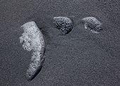 Three stones in the black sand
