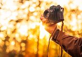 Man Hand Holding Retro Photo Camera Outdoor Lifestyle Concept With Sun Lights Bokeh Autumn Nature On