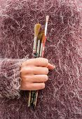 holding bunch of paint brushes