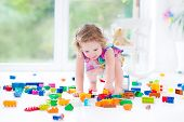 Funny Blond Toddler Girl With Curly Hair Sitting On A Floor In A Toy Mess In A Sunny White Bedroom