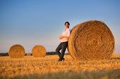 Beautiful Young Pregnant Woman Relaxing In A Hay Bales Field At Sunset