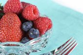 Bowl Of Strawberries, Blueberries And Raspberries With Fork And Pale Blue Napkin.