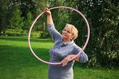 Portrait of happy pretty senior woman exercising with colorful hula hoop on nature background