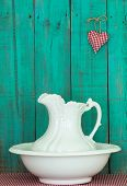 Antique water pitcher and basin by rustic teal blue wooden background