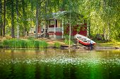 stock photo of old boat  - Summer cottage by the lake in rural Finland