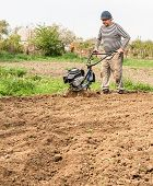 picture of plowed field  - Farmer plowing the field - JPG