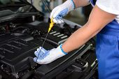 stock photo of grease  - Side view of mechanic checking motor oil in a car with open hood - JPG