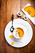Vegetable Cream Soup With Whipped Cream And Pumpkin Seeds On Wooden Table.