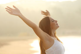 picture of breathing exercise  - Relaxed woman breathing fresh air raising arms at sunrise with a warmth golden background - JPG