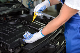 picture of grease  - Side view of mechanic checking motor oil in a car with open hood - JPG