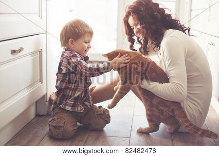 Mother with her child playing with pet on the floor at the kitchen at home