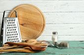 Wooden utensils with metal grater and cutting board on color table and planks background