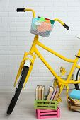 Bicycle with books in crate on brick wall background
