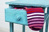 Socks in color drawer on white brick wall background