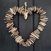 image of driftwood  - Driftwood heart hanging on a dark oak wood background - JPG