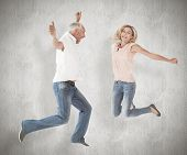 Excited couple cheering and jumping against weathered surface