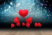 Red love hearts against shimmering light design over boards
