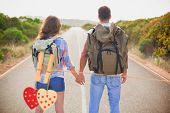 Hiking couple standing on countryside road against hearts hanging on the line