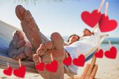 Close up of sandy feet of couple in a hammock against hearts hanging on a line