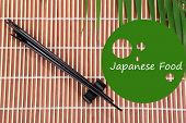 Pair of chopsticks and Japanese Food text on bamboo mat background