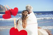 Couple wrapped up in blanket on the beach looking out to sea against hearts hanging on a line