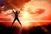 Fit blonde jumping with arms outstretched against sunrise over grass