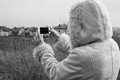 woman takes photos of country town