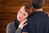 Scared woman holding onto man against overhead of wooden planks