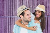 Happy casual man giving pretty girlfriend piggy back against wooden background in purple