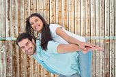 Happy casual man giving pretty girlfriend piggy back against wooden background in pale wood