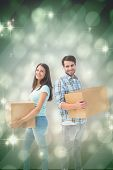 Happy young couple with moving boxes against light design shimmering on green