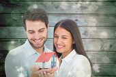 Attractive young couple holding a model house against light design shimmering on green