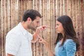 Angry couple pointing at each other against wooden planks