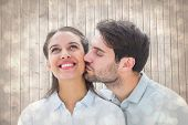 Handsome man kissing girlfriend on cheek against light glowing dots design pattern
