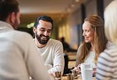 people, leisure, communication, eating and drinking concept - happy friends meeting and drinking tea or coffee at cafe