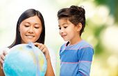 family, children, travel, geography and happy people concept - mother and daughter with globe over green background