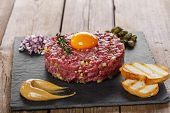 Beef tartare with capers and onions yolk with mustard