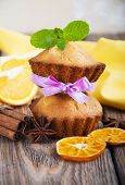 stock photo of bakeshop  - Homemade Muffins Ready for Breakfast with orange slices and cinnamon sticks on a wooden background - JPG