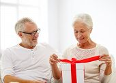 family, holidays, christmas, age and people concept - happy senior couple with gift box over white room background