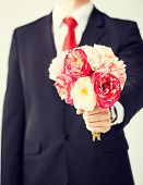 close up of young man giving bouquet of flowers.